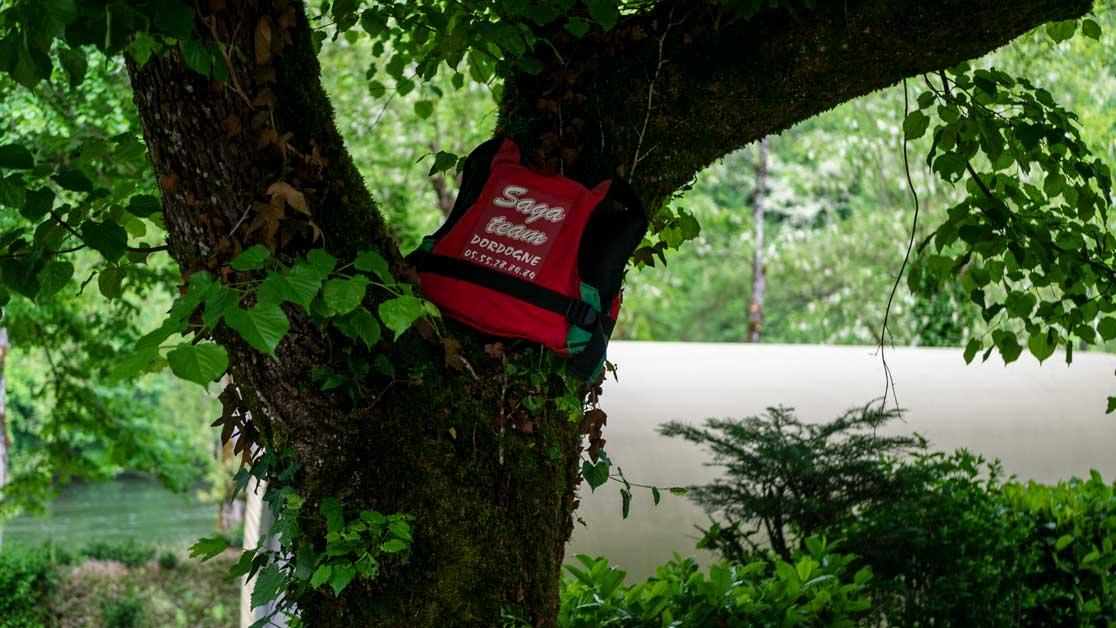 Gilet de sauvetage de la Saga Team dordogne avec en fond de la verdure et le fleuve la Dordogne
